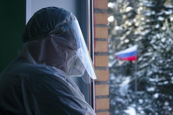 """Alexander Romanov, chief physician of the hospital in Sortavala wearing protective gear looks through a window of a local rural medical post in the village of Ikhala in Russia's Karelia region, Tuesday, Feb. 16, 2021. Russia's rollout of its coronavirus vaccine is only now picking up speed in some of its more remote region. Romanov acknowledged that """"the number of vaccinated people is not high,"""" but is convinced more doses will arrive soon. (AP Photo/Dmitri Lovetsky)"""