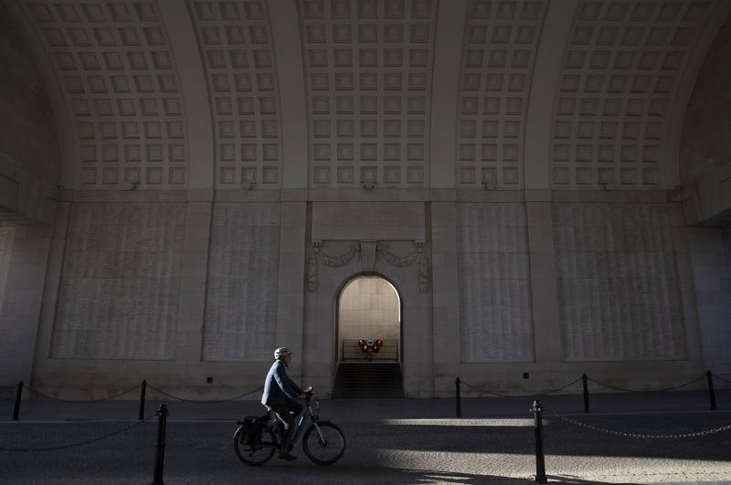 In this April 25, 2020, a man cycles under the World War I monument, Menin Gate, in Ypres, Belgium. As countries across the world seek to get their economies back on track after coronavirus lockdowns are over, some people are encouraging the use of bicycles as a way to avoid unsafe crowding on trains and buses.  (AP Photo/Virginia Mayo)