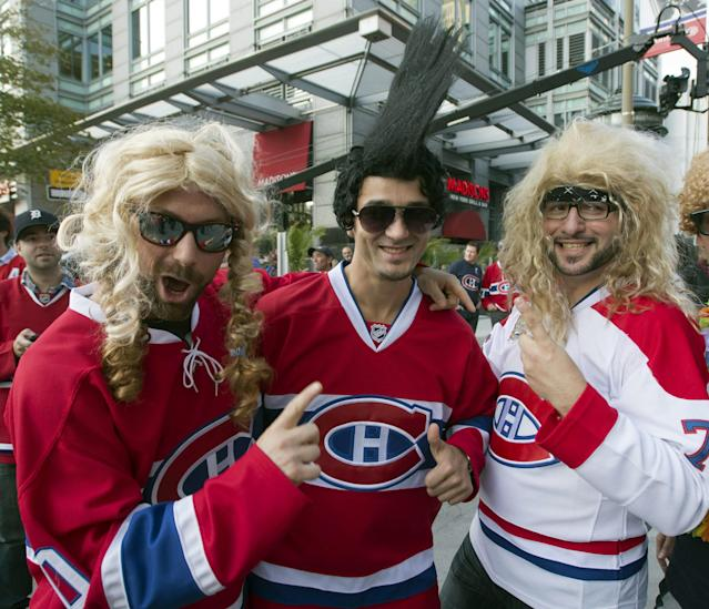 Montreal Canadiens fans, from left, Jonathan Lamothe, Miguel Plourde and Dominique Petit gesture and wear funny wigs as they take part in pregame festivities before the season-opening NHL hockey game between the Toronto Maple Leafs and the Montreal Canadiens, Tuesday, Oct. 1, 2013, in Montreal. (AP Photo/The Canadian Press, Ryan Remiorz)