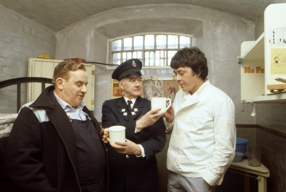 "Old lag Fletcher (Ronnie Barker), fellow prisoner Godber (Richard Beckinsale) and prison officer Mackay (Fulton Mackay) during location shooting for the film version of their TV series ""Porridge"" at Chelmsford Jail, which has been empty since a fire last year.   (Photo by PA Images via Getty Images)"