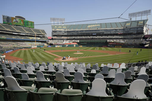 Cutouts are seated at Oakland Coliseum as Chicago White Sox's Dallas Keuchel, center, pitches to Oakland Athletics' Tommy La Stella during the first inning of Game 2 of an American League wild-card baseball series Wednesday, Sept. 30, 2020, in Oakland, Calif. (AP Photo/Eric Risberg)
