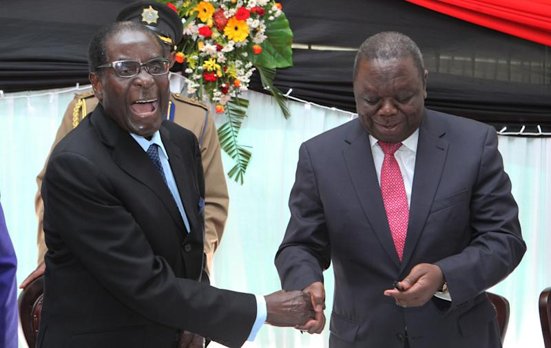 "FILE - In this May 22, 2013 file photo Zimbabwean President Robert Mugabe, left, shakes hands with Prime Minister Morgan Tsvangirai after he signed the new constitution into law at State house in Harare. Zimbabwe's increasingly popular 'mole' blogger, Baba Jukwa, dishes out dirt on the president's party. Baba Jukwa, is a ZANU-PF party insider, or ""mole,"" who says on his popular Facebook page that he is disheartened by the ""corrupt and evil machinations"" of President Robert Mugabe's fractious party. The faceless Jukwa vows to end Mugabe's rule by exposing the alleged involvement of his top officials, secret agents, police and military in the violence that led to disputed elections in 2008 and corruption and internal plotting ever since. (AP Photo/Tsvangirayi Mukwazhi, File)"