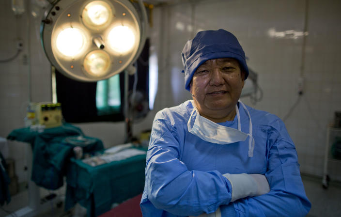 """In this Oct. 23, 2013 photo, Nepalese master surgeon Sandut Ruit poses at a government hospital in Bago, Myanmar. Ruit estimates sight has been restored to 3-4 million people through his assembly-line approach. Once condemned by the international medical community as unthinkable and reckless, this mass surgery """"in the bush"""" started spreading from Nepal to poor countries worldwide nearly two decades ago. (AP Photo/Gemunu Amarasinghe)"""