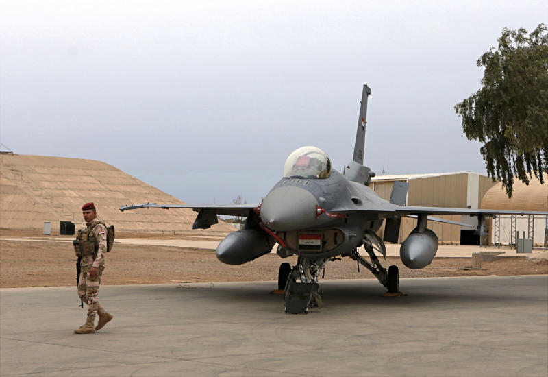 FILE - in this Tuesday, Feb. 13, 2018 file photo, an Iraqi army soldier stand guard near a U.S.- made Iraqi Air Force F-16 fighter jet at the Balad Air Base, Iraq. Militants fired early Saturday, June 15, 2019,  three mortar shells on an air base just north of Baghdad where American trainers are present, causing a small fires but no casualties, the Iraqi military said. (AP Photo/Khalid Mohammed, File)