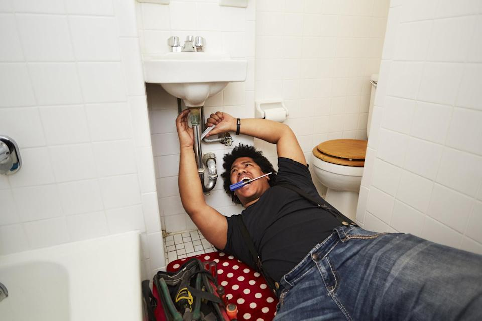 A guy on the floor underneath a bathroom sink working on it with a tool, holding a screwdriver in his mouth