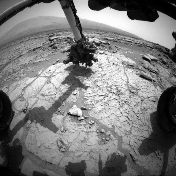 The percussion drill in the turret of tools at the end of the robotic arm of NASA's Mars rover Curiosity has been positioned in contact with the rock surface in this image from the rover's front Hazard-Avoidance Camera (Hazcam). The drill was