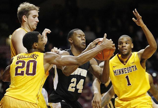 Wofford forward Justin Gordon (24) tries to hold onto a rebound from Minnesota guard Austin Hollins (20) and guard Andre Hollins (1) in the first half of an NCAA college basketball game Thursday, Nov. 21, 2013, in Minneapolis. (AP Photo/Stacy Bengs)