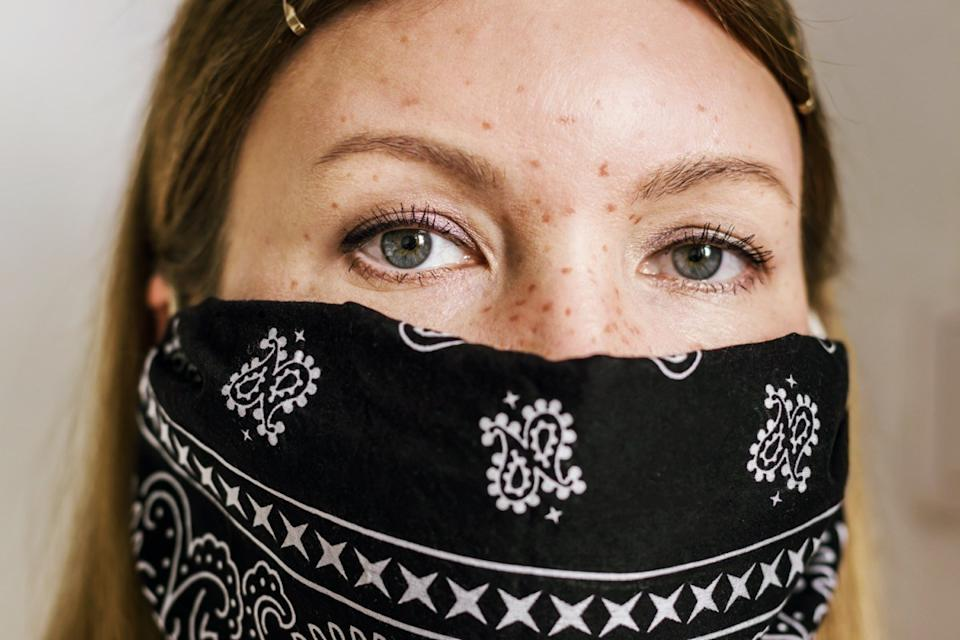 woman with freckles wearing black bandana face mask