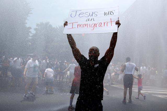 <p>Jonathan Reed of Silver Spring, Maryland, holds up a sign as he stands in a spray of water from a fire truck during rally by immigration activists to protest against the Trump Administration's immigration policy outside the White House in Washington,D.C., June 30, 2018. (Photo: Joshua Roberts/Reuters) </p>