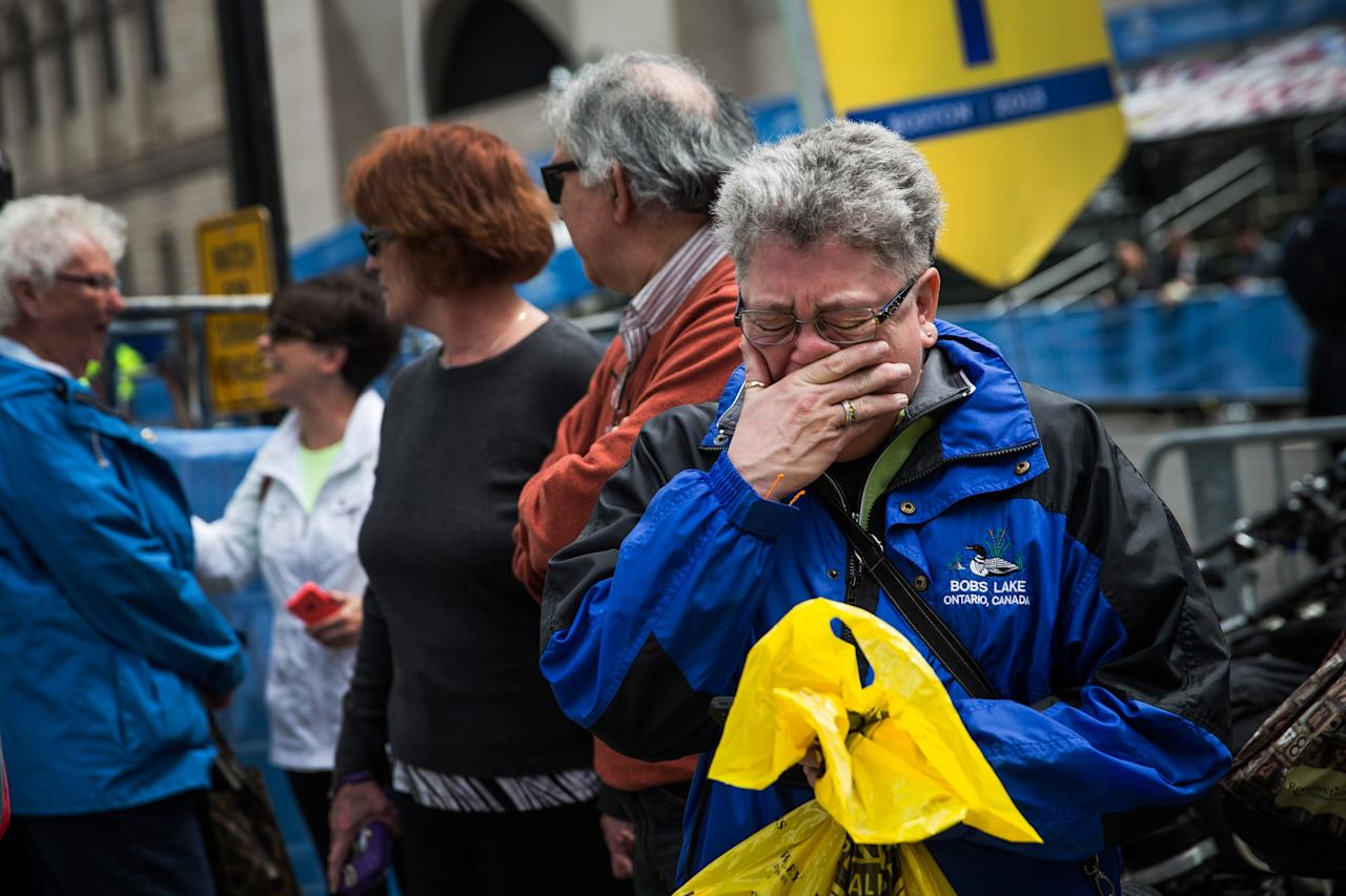 BOSTON, MA - APRIL 15: Sharon Neary, of Rochester, New York, cries while watching a billboard television screen broadcasting the ceremony commemorating the one year anniversary of the 2013 Boston Marathon Bombing , on April 15, 2014 in Boston, Massachusetts. Last year, two pressure cooker bombs killed three and injured an estimated 264 others during the Boston marathon, on April 15, 2013. Neary says she was standing near the site of the bombing before it went off. (Photo by Andrew Burton/Getty Images)