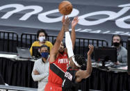 Portland Trail Blazers guard CJ McCollum, left, hits a shot over Houston Rockets forward Danuel House Jr. to give the Blazers the lead late in overtime of an NBA basketball game in Portland, Ore., Saturday, Dec. 26, 2020. The Blazers won 128-126 (AP Photo/Steve Dykes)