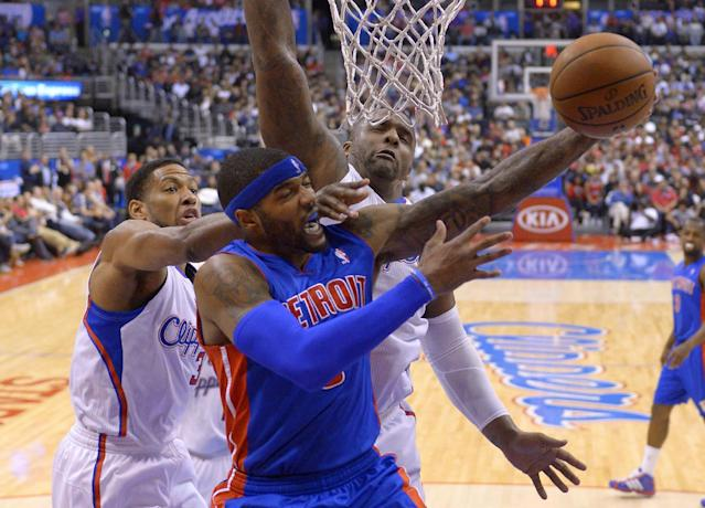 Detroit Pistons forward Josh Smith, center, shoots as Los Angeles Clippers guard Willie Green, left, and forward Glen Davis defend during the first half of an NBA basketball game, Saturday, March 22, 2014, in Los Angeles. (AP Photo/Mark J. Terrill)
