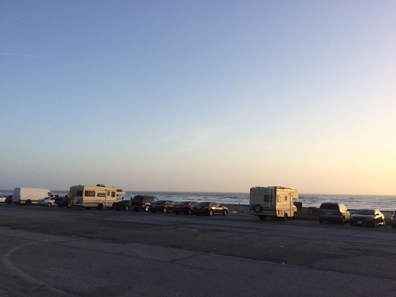 Unhoused people living in RVs in the Ocean Beach parking lot.