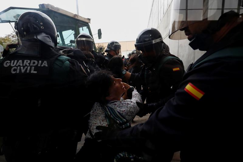 Spanish Civil Guard officers scuffle with a woman outside a polling station for the banned independence referendum.