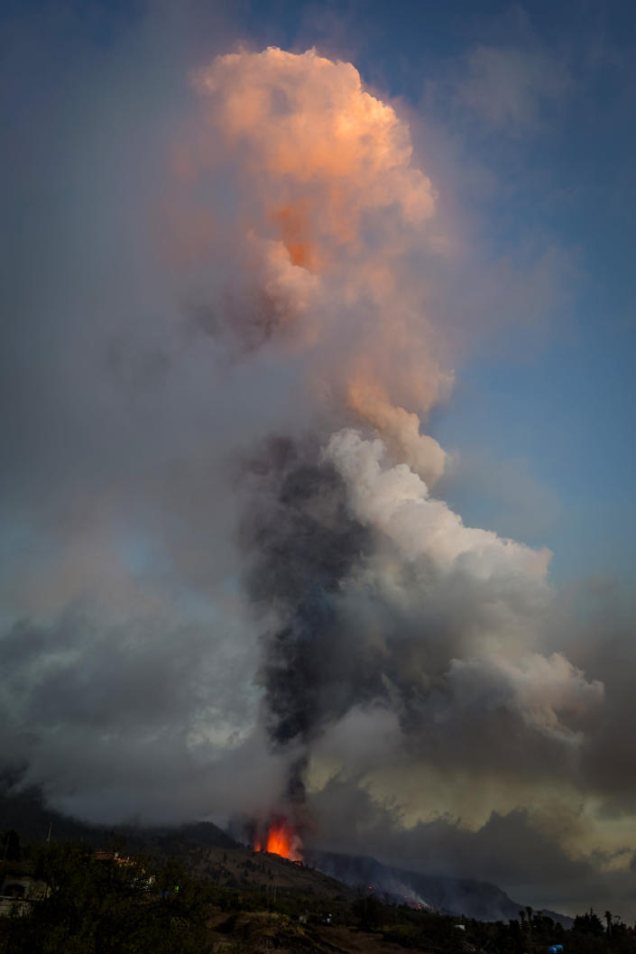 Lava and smoke flow from an eruption of a volcano at the island of La Palma in the Canaries, Spain, Sunday, Sept. 19, 2021. A volcano on Spain's Atlantic Ocean island of La Palma erupted Sunday after a weeklong buildup of seismic activity, prompting authorities to evacuate thousands as lava flows destroyed isolated houses and threatened to reach the coast. New eruptions continued into the night. (AP Photo/Jonathan Rodriguez)