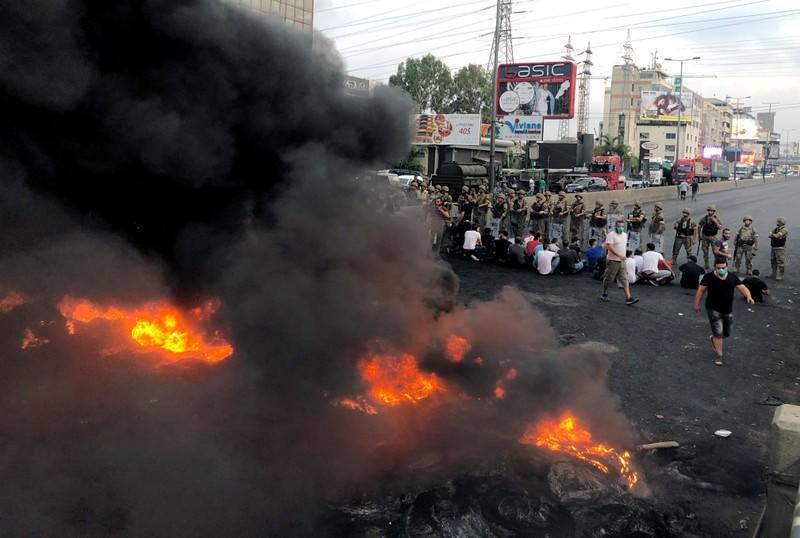 Demonstrators sit together during a protest over deteriorating economic situation, in the city of Jounieh