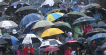 Spectators take cover under umbrellas a heavy rain falls as they watch golfers during the first round of the British Open Golf Championships at Royal Portrush in Northern Ireland, Thursday, July 18, 2019.(AP Photo/Jon Super)