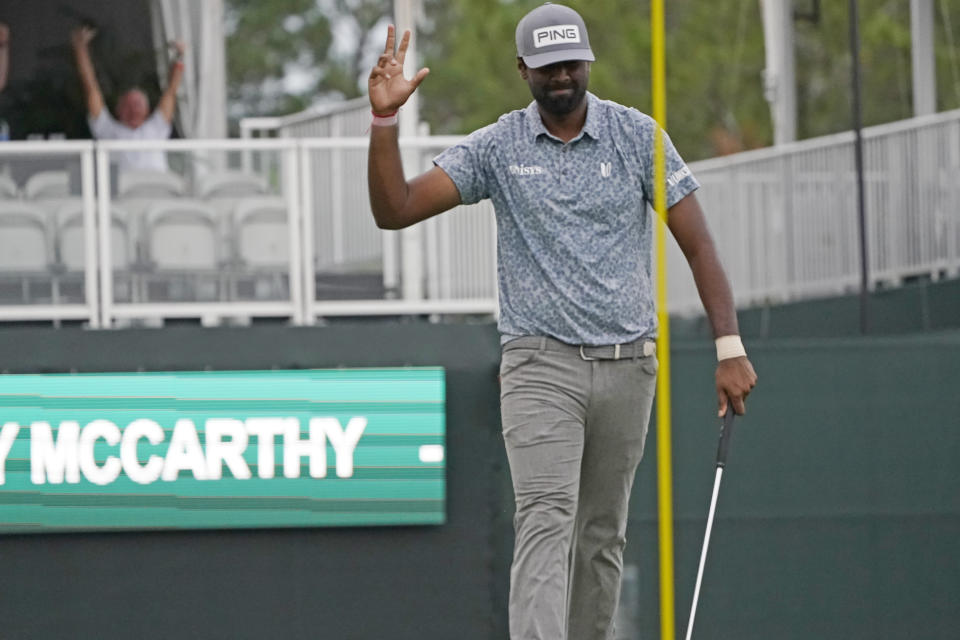 Sahith Theegala acknowledges a fan's cheer in the background following his sinking a birdie putt drop on the 18th hole during the second round of the Sanderson Farms Championship golf tournament in Jackson, Miss., Friday, Oct. 1, 2021. Theegala finished the day in a three-way tie at 13-under. (AP Photo/Rogelio V. Solis)