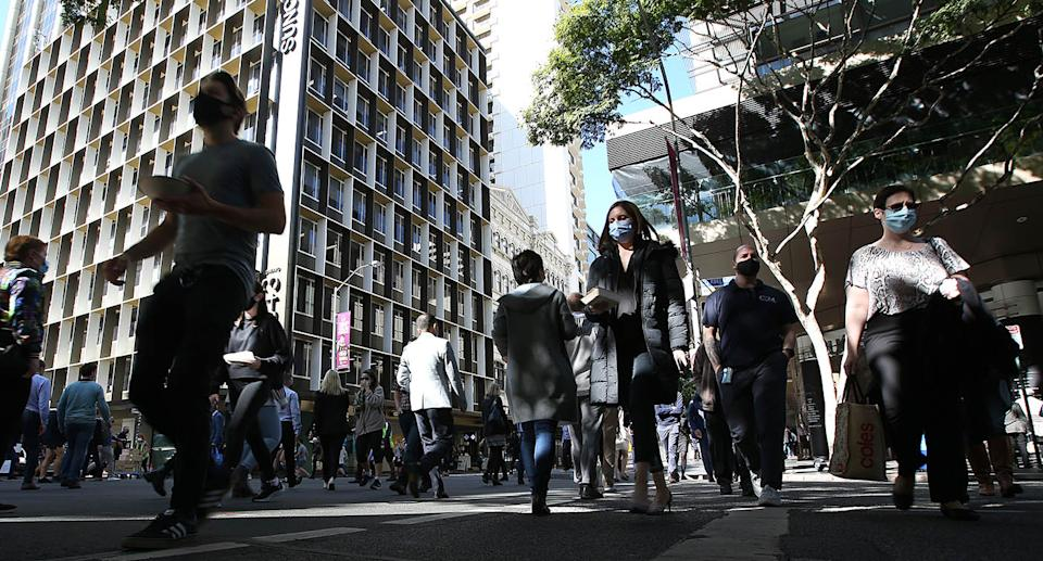 A photo of a Brisbane street in the city showing people walking and wearing masks.