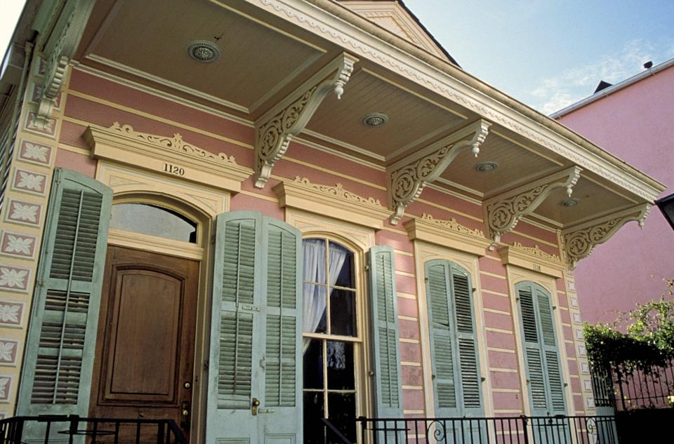 The exterior of a Creole cottage with Victorian trimmings on New Orleans's Dauphine Street in the French Quarter.