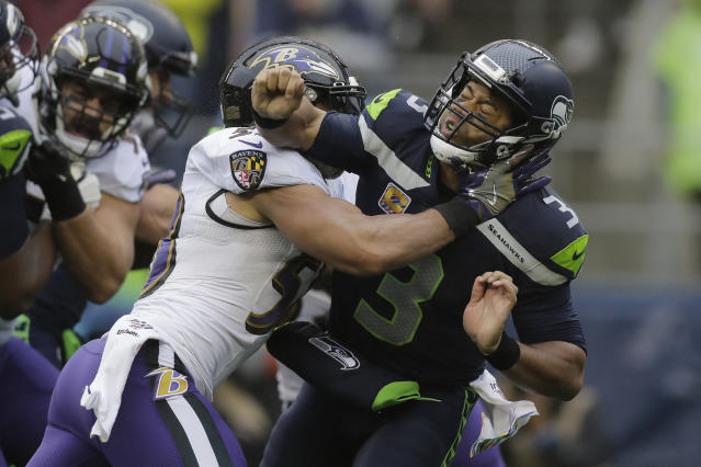 Seattle Seahawks quarterback Russell Wilson (3) is hit after he passed under pressure from Baltimore Ravens linebacker L.J. Fort, left, during the first half of an NFL football game, Sunday, Oct. 20, 2019, in Seattle. (AP Photo/John Froschauer)