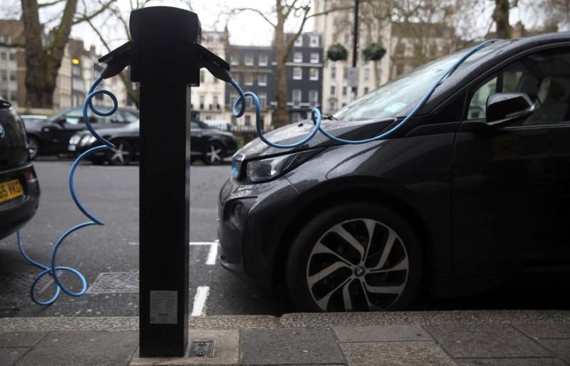 Electric cars are plugged into a charging point in London