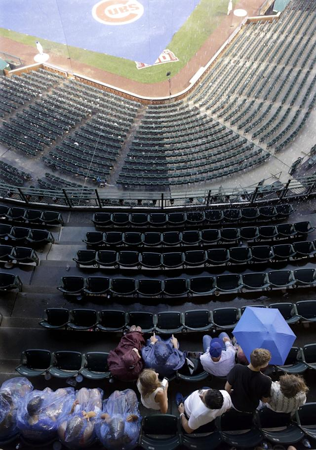 Baseball fans wait for a baseball game between the Baltimore Orioles and the Chicago Cubs during a rain delay in Chicago, Saturday, Aug. 23, 2014. (AP Photo/Nam Y. Huh)