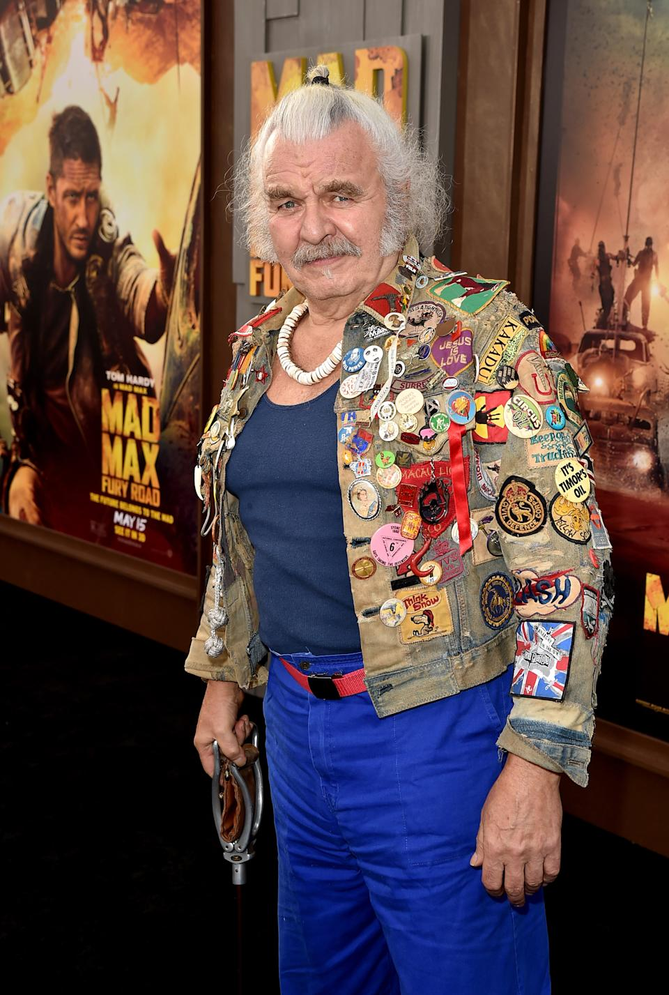 """Actor Hugh Keays-Byrne wearing blue pants and a jacked covered in colourful patches at the premiere of Warner Bros. Pictures' """"Mad Max: Fury Road"""" at TCL Chinese Theatre on May 7, 2015 in Hollywood, California."""