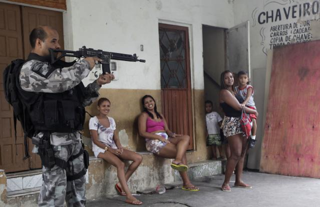 Residents observe a police officer take up position during an operation at the Mare slums complex in Rio de Janeiro March 25, 2014. Brazil will deploy federal troops to Rio de Janeiro to help quell a surge in violent crime following attacks by drug traffickers on police posts in three slums on the north side of the city, government officials said on Friday. Less than three months before Rio welcomes tens of thousands of foreign soccer fans for the World Cup, the attacks cast new doubts on government efforts to expel gangs from slums using a strong police presence. The city will host the Olympics in 2016. REUTERS/Ricardo Moraes (BRAZIL - Tags: CRIME LAW)