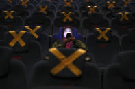 A customer uses her mobile phone before the start of a movie show as she sits amid physical distancing markers during the first day of reopening at a cinema in Jakarta, Indonesia, Thursday, Sept. 16, 2021. Cinemas in several cities shut during the deadly wave of coronavirus outbreak that hit the country in July were allowed to begin reopening with capacity limit as cases decline. (AP Photo/Tatan Syuflana)