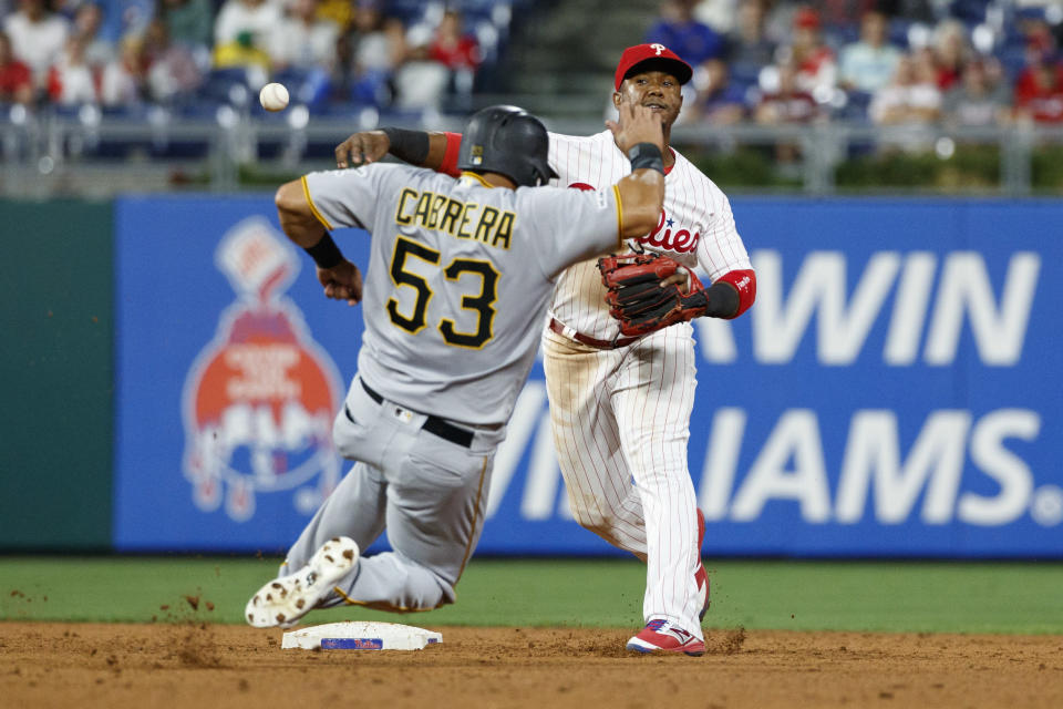 Philadelphia Phillies shortstop Jean Segura, right, throws to first base after forcing out Pittsburgh Pirates' Melky Cabrera at second on a ball hit by Kevin Newman during the ninth inning of a baseball game, Tuesday, Aug. 27, 2019, in Philadelphia. Newman was safe at first on an error by Rhys Hoskins. Pittsburgh won 5-4. (AP Photo/Matt Slocum)