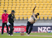 New Zealand's Ish Sodhi, right, bowls as Australia's Aaron Finch, center, watches during the 4th T20 cricket international match at Wellington Regional Stadium in Wellington, New Zealand, Friday, March 5, 2021. (John Cowpland/Photosport via AP)