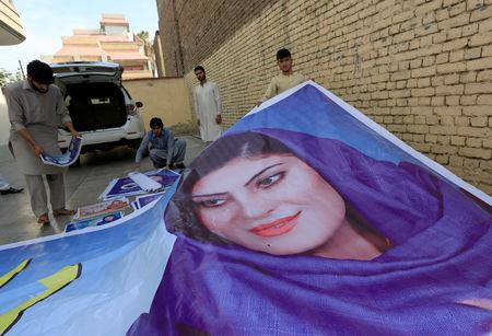 Supporters of female Afghan parliamentary election candidate, Dewa Niazai, prepare to install a poster of her during a election campaign in Jalalabad, Afghanistan October 4, 2018.  REUTERS/Parwiz