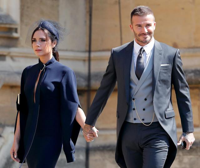 Victoria Beckham, pictured with husband David at the royal wedding, got grief over her neutral facial expression. (Photo: Max Mumby/Indigo/Getty Images)