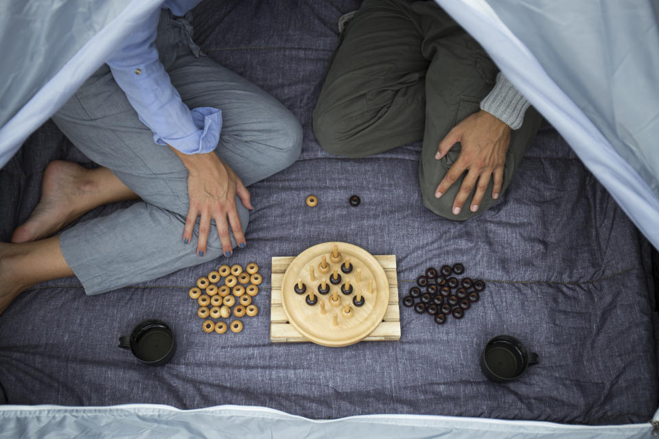 Couple sitting in tent playing board game, partial view