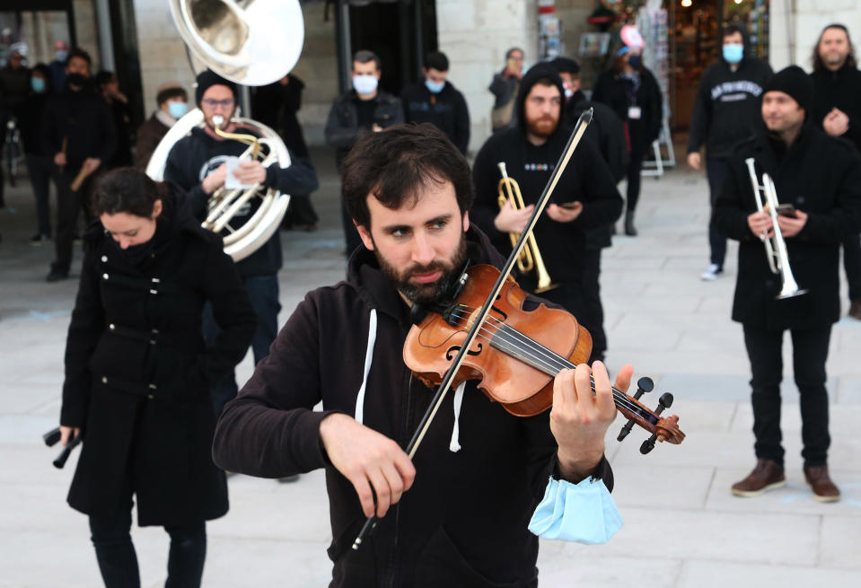 Professional musicians dressed in black perform on the Place of Freedom in Bayonne, southwestern France, Saturday, Nov. 28, 2020, as they stage a protest against the nation wide lockdown. They are not authorized to resume their activities in the measures announced by President Macron. (AP Photo/Bob Edme)