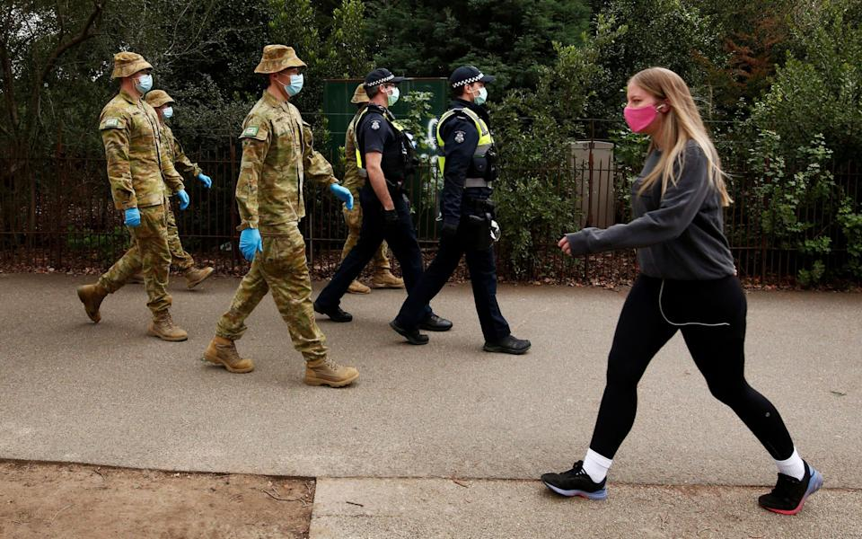 ADF personnel and Victorian police officers patrol a walking track as Melbourne remains in lockdown restrictions - Reuters
