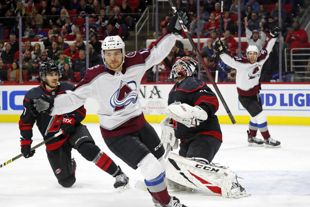 Colorado Avalanche's Tyson Jost (17) celebrates his goal against Carolina Hurricanes goaltender Anton Forsberg, second from right, with Hurricanes' Trevor van Riemsdyk (57) nearby during the first period of an NHL hockey game in Raleigh, N.C., Friday, Feb. 28, 2020. (AP Photo/Karl B DeBlaker)