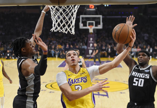 Lonzo Ball (C) goes to the hole against Kings guard De'Aaron Fox (L) on Tuesday night. (AP)