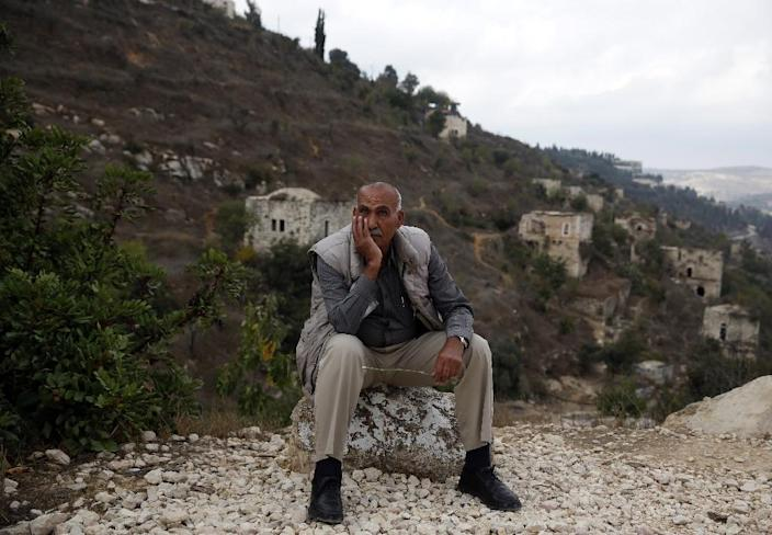 Yacoub Odeh, a 77-year-old Palestinian, sits by old houses in the ghost village of Lifta, whose Palestinian inhabitants fled during fighting in the 1948 war surrounding the creation of Israel (AFP Photo/AHMAD GHARABLI)
