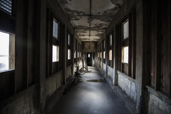 <p>A corridor leading to the hospital wards to Island Three of Ellis Island. The wards are filled with long and short corridors that are filled eerie shadows and soft light. (Photo: Gordon Donovan/Yahoo News) </p>