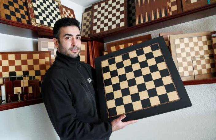David Ferrer poses with a chessboard at the Rechapados Ferrer factory in La Garriga