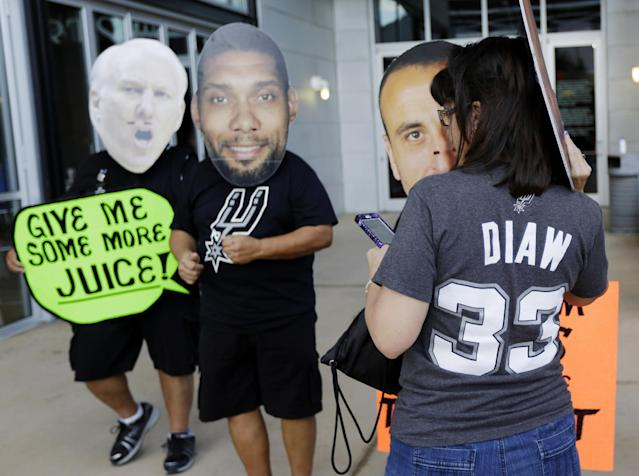 San Antonio Spurs fans wearing faces from left of head coach Gregg Popovich, plus players Tim Duncan and Manu Ginobili gather to take a picture before Game 1 of the NBA basketball finals against the Miami Heat on Thursday, June 5, 2014, in San Antonio. (AP Photo/Eric Gay)