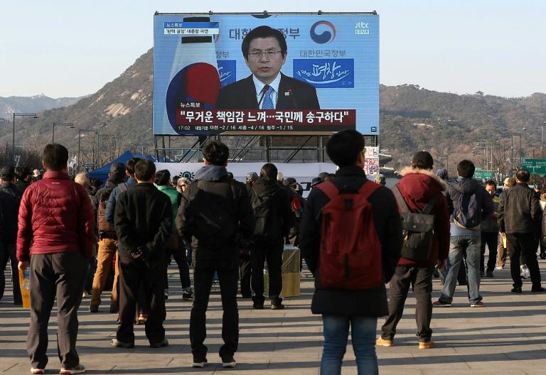 People watch a live broadcast showing South Korea's Acting President and Prime Minister Hwang Kyo-Ahn delivering a public address in Seoul on March 10, 2017