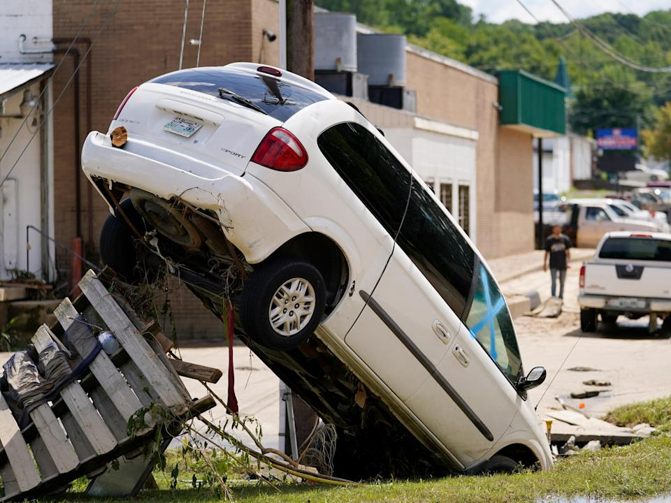 A car flipped upside-down and supporterd by a utility pole in Waverly, Tennessee, the morning after the devastating flooding (Mark Humphrey/AP)