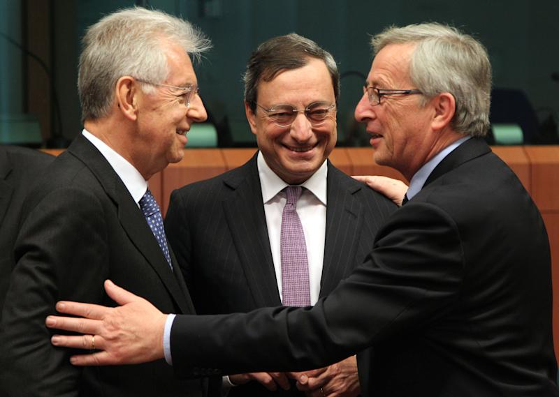President of the European Central Bank Mario Draghi, center, smiles, as he talks with Italy's Prime and Finance Minister Mario Monti, left, and Luxembourg's Prime Minister and chairman of the Eurogroup, Jean-Claude Juncker, during the Eurogroup ministerial meeting at the European Council building in Brussels, Monday, May 14, 2012. (AP Photo/Yves Logghe)