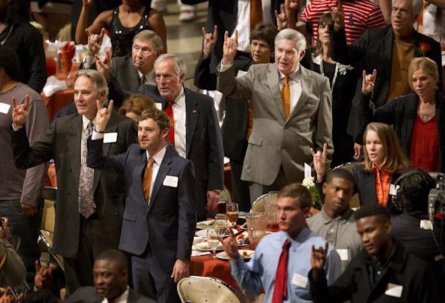 Texas head coach Mack Brown, right in gray suit, stands for the school song during the University of Texas Longhorns Honors banquet at the Frank Erwin Center in Austin on Friday Dec.13, 2013. At left is the new Texas Athletic Director Steve Patterson. (AP Photo/Austin American-Statesman, Jay Janner)