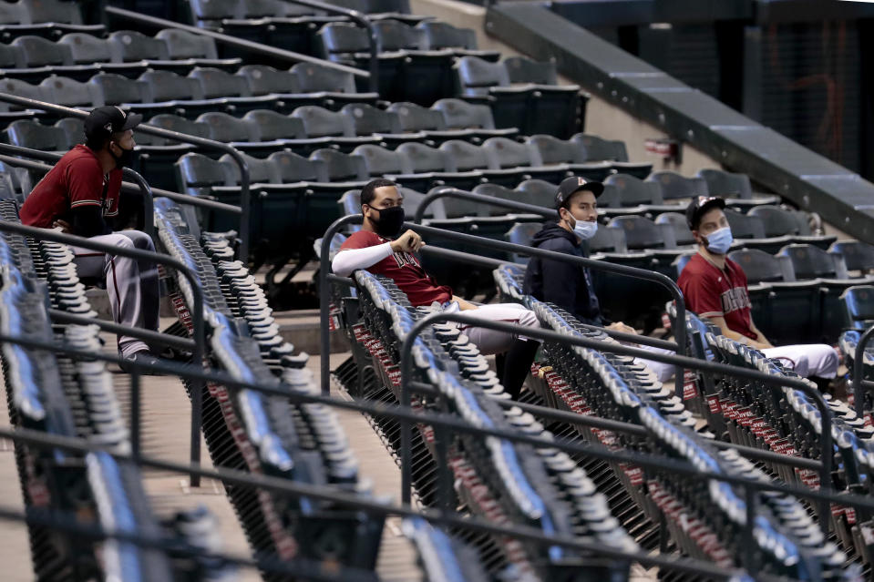 FILE - In this July 16, 2020, file photo, Arizona Diamondbacks players watch from the stadium seats during an intrasquad game at Chase Field, in Phoenix. MLB has provided teams with a 113-page operations manual detailing protocols for its pandemic-shortened 60-game regular season. Players will be tested every 48 hours. Masks and social distancing are a must at all times, except on the field. Backups will watch games from the stands instead of the dugout. No sunflower seeds. No spitting. No licking fingers. (AP Photo/Matt York, File)