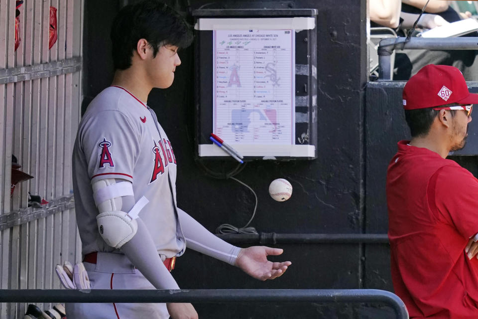 Los Angeles Angels designated hitter Shohei Ohtani, of Japan, plays with a ball in the dugout during the second inning of a baseball game against the Chicago White Sox in Chicago, Thursday, Sept. 16, 2021. (AP Photo/Nam Y. Huh)