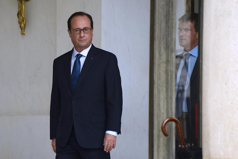 French President Francois Hollande (L) escorts French Prime Minister Manuel Valls from the Elysee presidential palace in Paris after a weekly cabinet meeting on August 27, 2014
